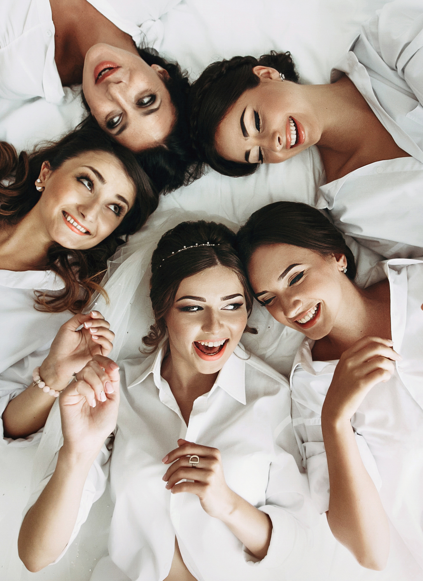 Sexy bride & bridesmaids lying in bed before wedding